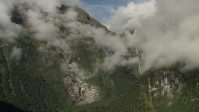 Fly through clouds in valley towards waterfall