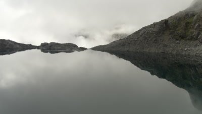 Flying over edge of high altitude lake, down waterfall through clouds