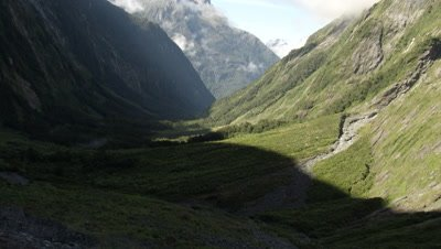 View of mountains and clouds through valley, pan right