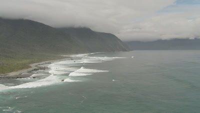 Flying low along coast as waves crash on shore