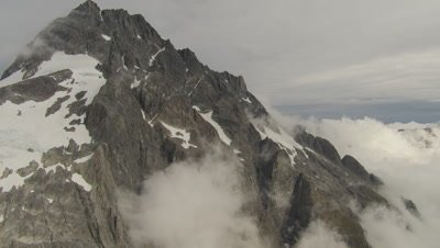 View of snowy mountains, pan left, cam flies over edge to reveal clouds and mountains in distance