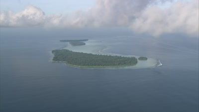 View of island through clouds, tilt down to high angle of island