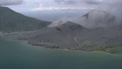 View of smoking volcano on coast