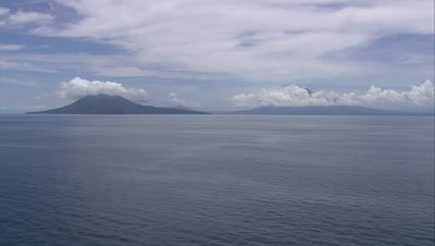 approach islands on horizon with cloud covered mountains