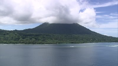 View of mountain on coast with clouds above it