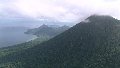 Island coast and mountain, camera rises into clouds