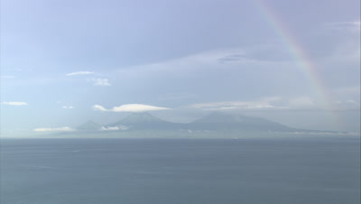 Island in distance with rainbow over it