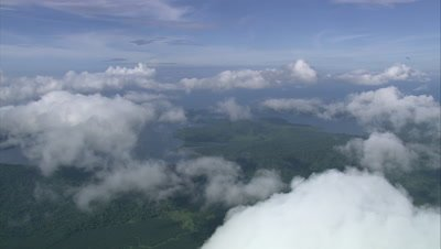 Island below clouds with palm oil plantation visible