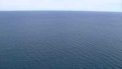 Ocean horizon, tilt down to buoy in water