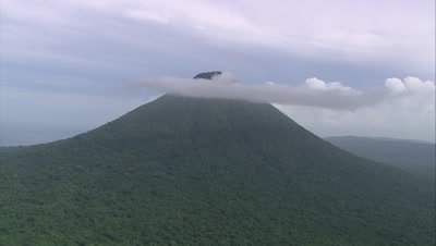 approaching mountain and clouds and flies over it revealing rest of island