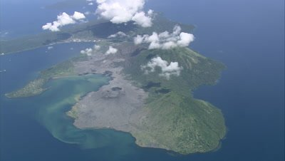 Approaching and tilting down on island with Volcano