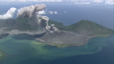 circling island as smoke spews out of volcano