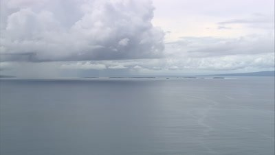 View of island coast with rain storm in distance