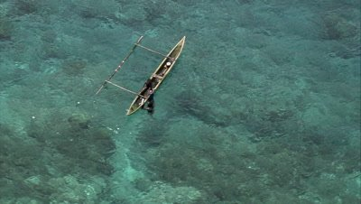 Indigenous people fishing over a coral reef