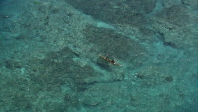 Indigenous people fishing over a coral reef; man shows off his catch of fish to the camera