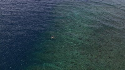 Indigenous person fishing over a coral reef on an island coastline