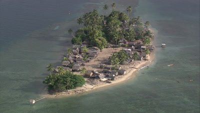 Aerial shot of a traditional village located on a small island in the South Pacific
