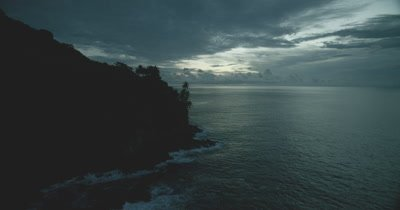 Passing edge of Cocos Island, rocky coast, with palm tree silhouettes in the foreground