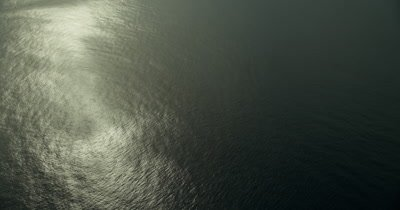Tilt up from ocean with sunlight reflecting off of it. Nice shadow contrast on water.