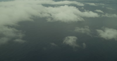 High angle on ocean, circling around clouds with sun reflecting off the surface of the water