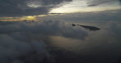 Flying by clouds over the ocean and island in the background