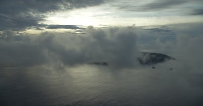 Flying through clouds to reveal island