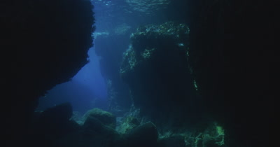Traveling through mysterious coastal rocky reef environment. Light rays shine down from surface