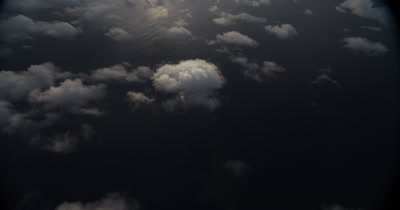 Slowly tilting from clouds to reveal Cocos island in the distance