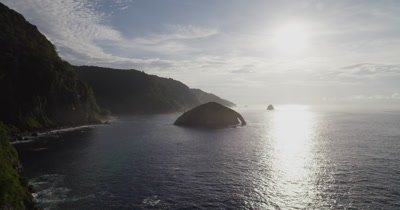 Flying past small island with arch towards sun