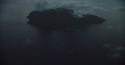 Clouds and island below, pan up to horizon from island.