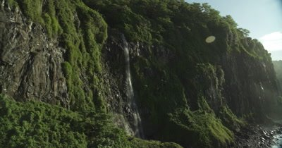 passing by waterfall on a cliff, camera turns directly towards the sun