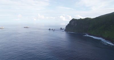 Flying along coast of Cocos Island, close to  water