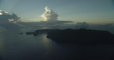 Circling island. Sun peaks through clouds in BG.