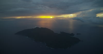 High angle of island and ocean with sun setting in background