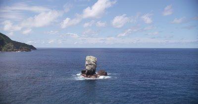 Circling rocks on coast. Waves crashing on rocks.