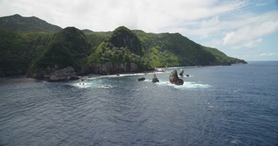 Approaching coast of tropical island with rock formations in the water