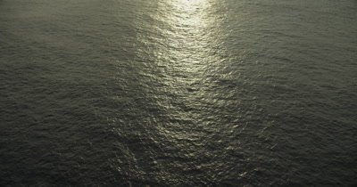 Travel over ocean, tilt up to reveal horizon. Sun reflecting off surface