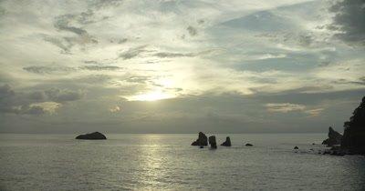 Island coast and horizon, tilt down to ocean.