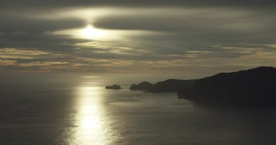 Track right from island to ocean. sun reflected on water