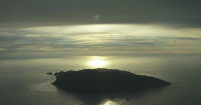 near static shot of island, sun reflecting off water