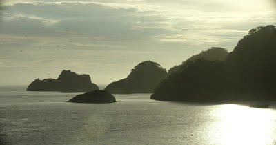 flying towards rock formations near islands coast
