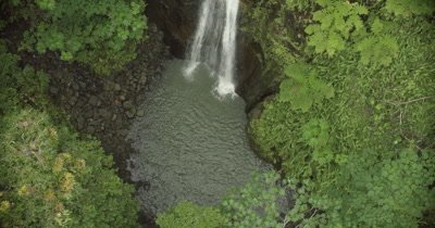 Zoom out to bird's eye view of waterfall spilling into a small pool