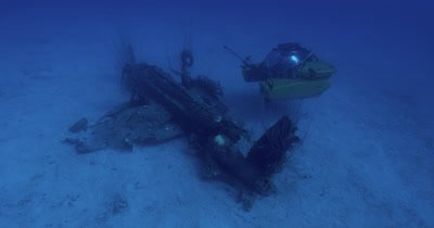 Tilt up from fish on propeller of plane wreck to submarine