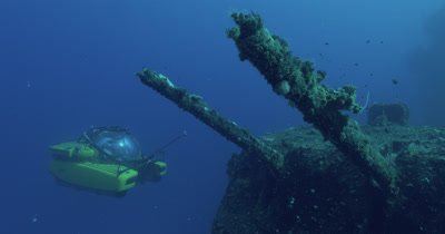submarine surveying guns, descending behind the wreck and exiting frame.
