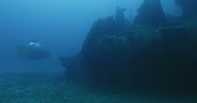 submarine enters from behind ship and shines light on wreckage