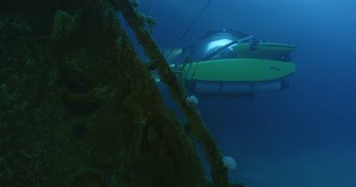 Tracking submarine shining light on edge of wreck.