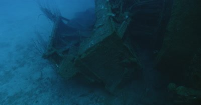 Pan from partially collapsed wreck to submarine.