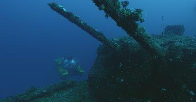 submarine ascending behind turret guns of USS Saratoga