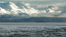 Tanker Anchored In Bay Under Beautiful Snow Covered Mountains, Wide Shot With Sea Ice In Foreground