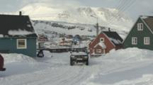 Truck And Snowmobile Drive Through Village In Rugged Snowy Area At Base Of Mountain